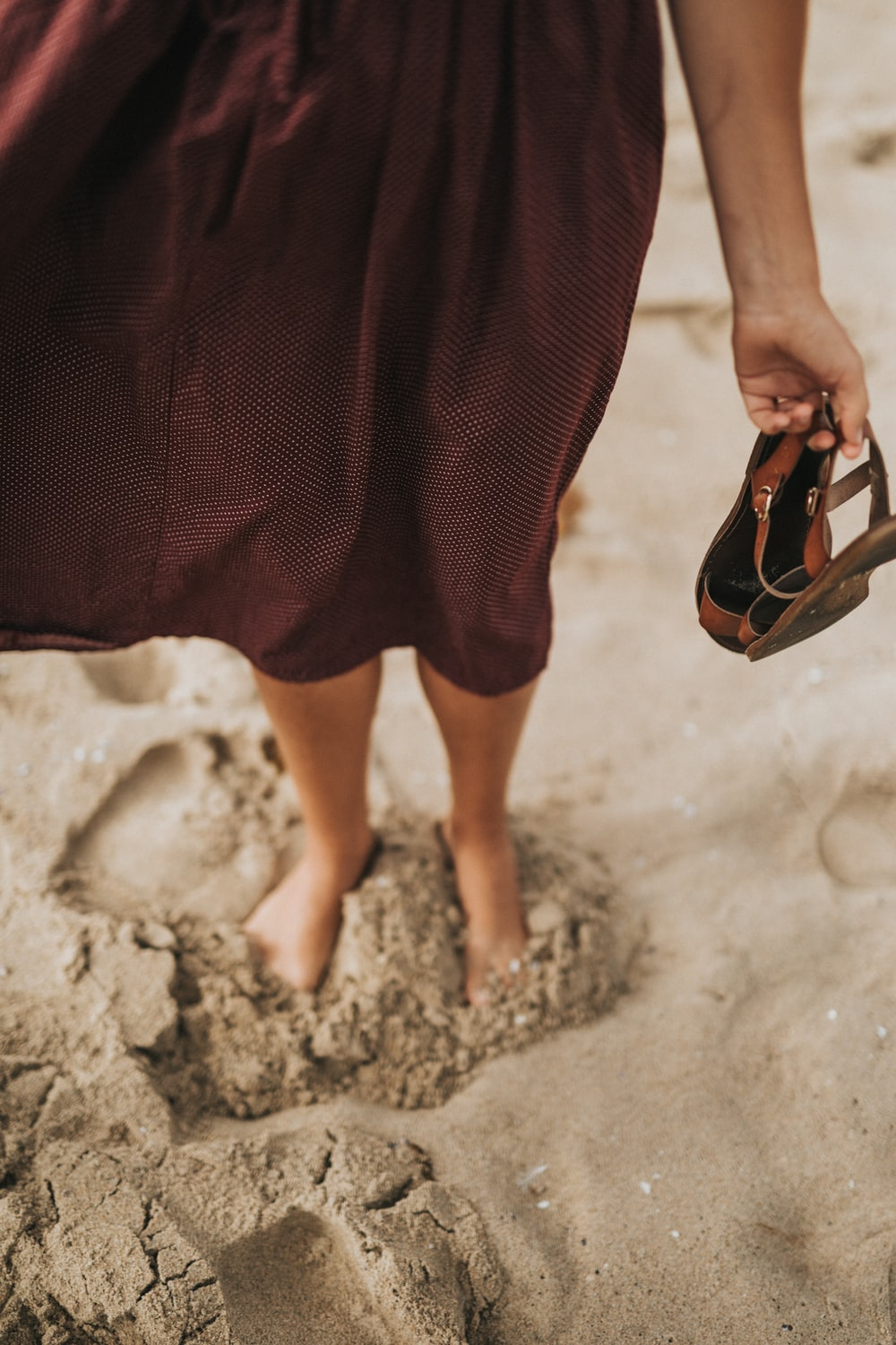 woman stepping on brown sand