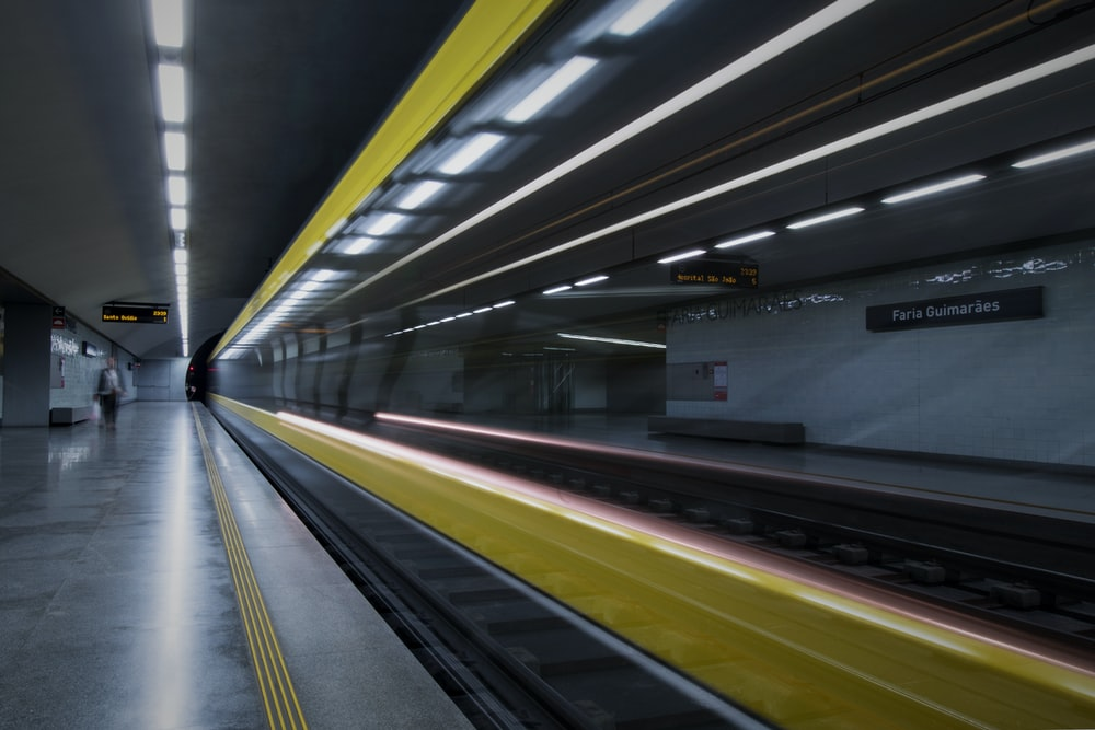person standing near the train rails inside the tunnel