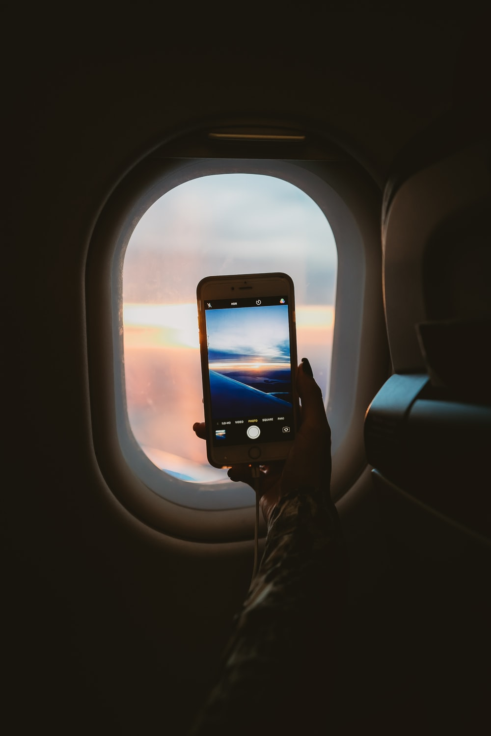 person taking picture of window plane