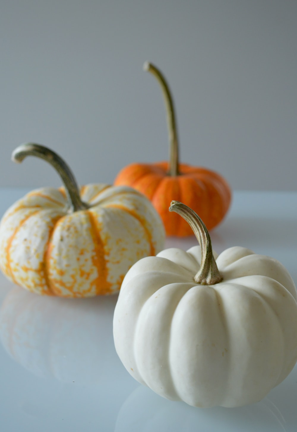 two white and one orange pumpkins on white surface