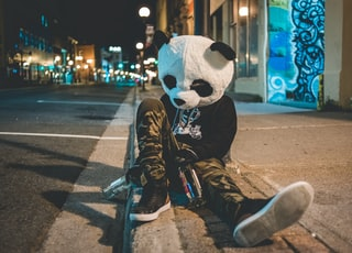 man wearing panda costume leaning on post