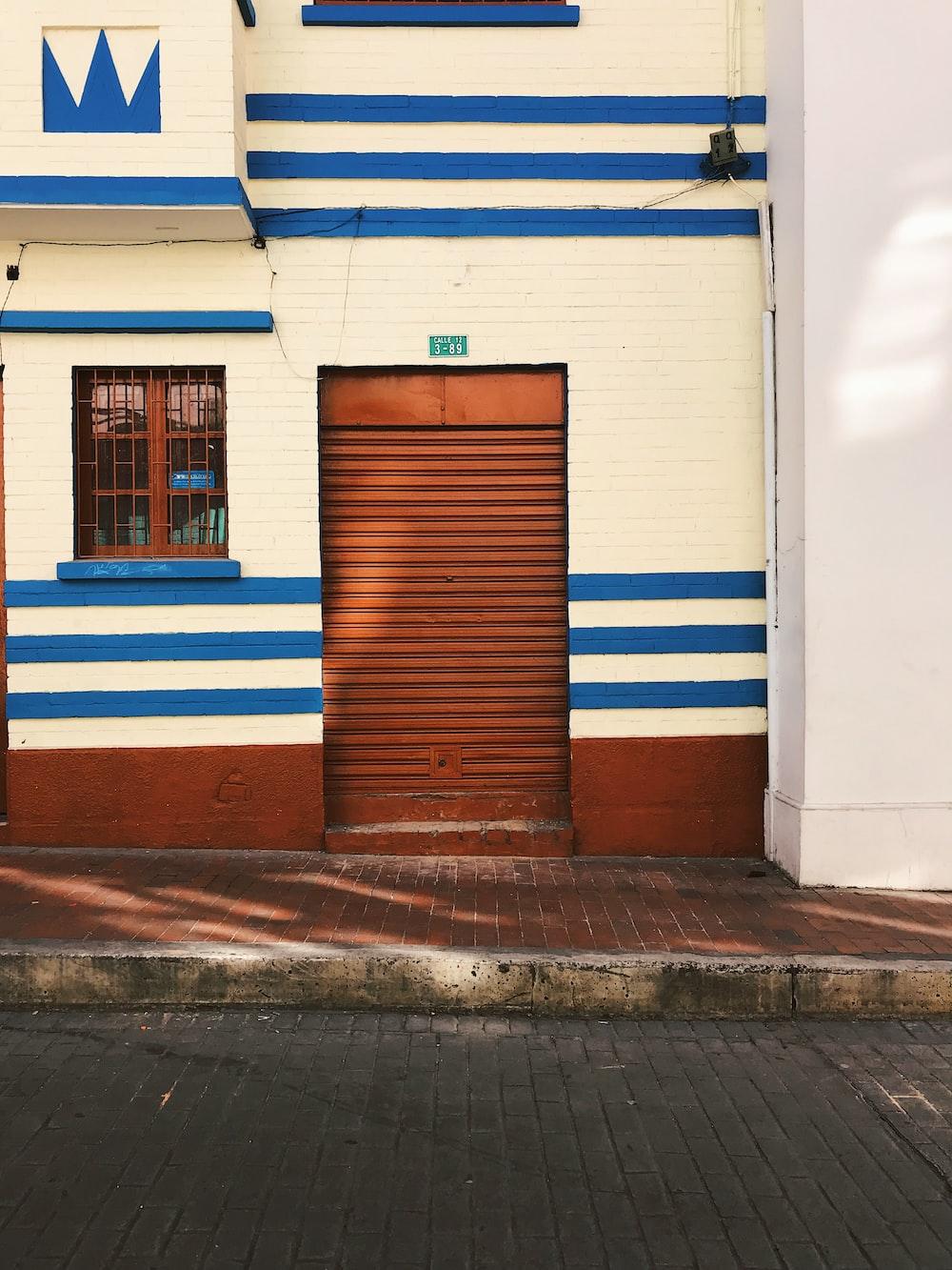 empty sidewalk beside closed brown door