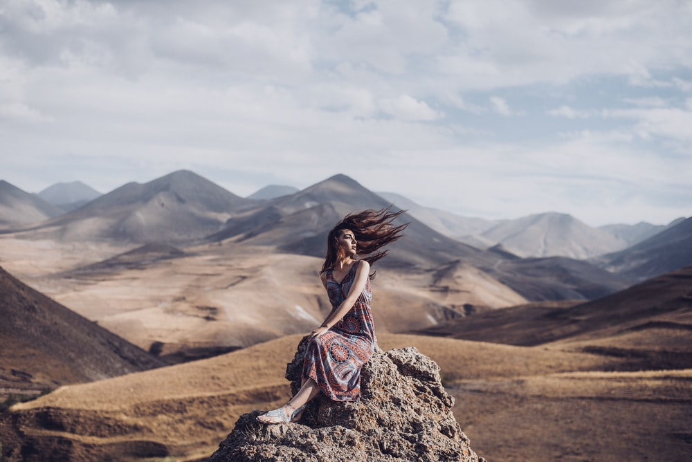 woman sitting on rock with hair blown by air
