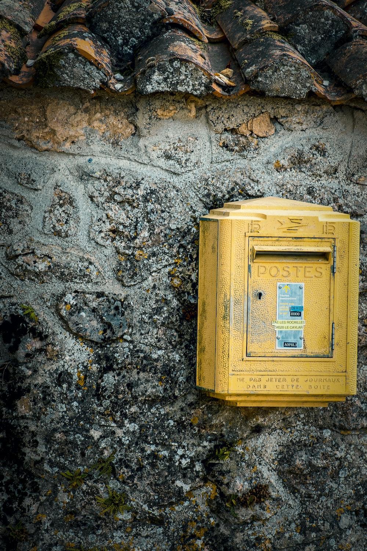 yellow mail box hung on gray wall