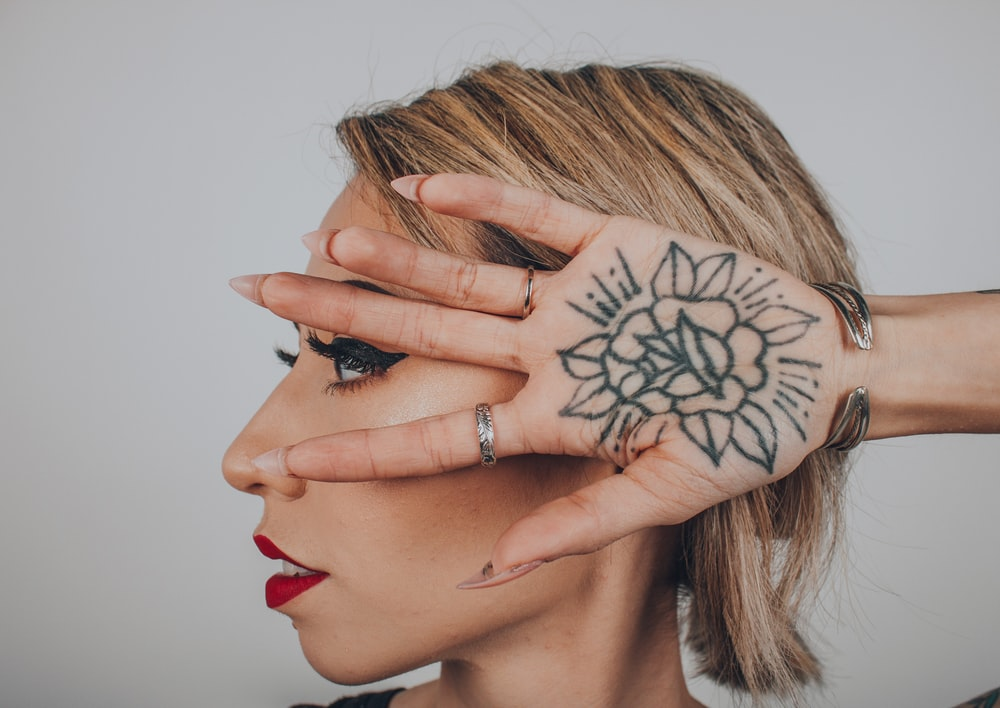 woman with black flower tattoo in palm