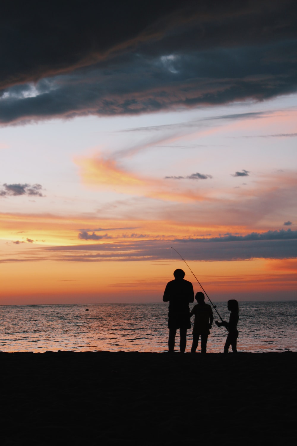 silhouette of children and man standing on shore with fishing rod during golden hour