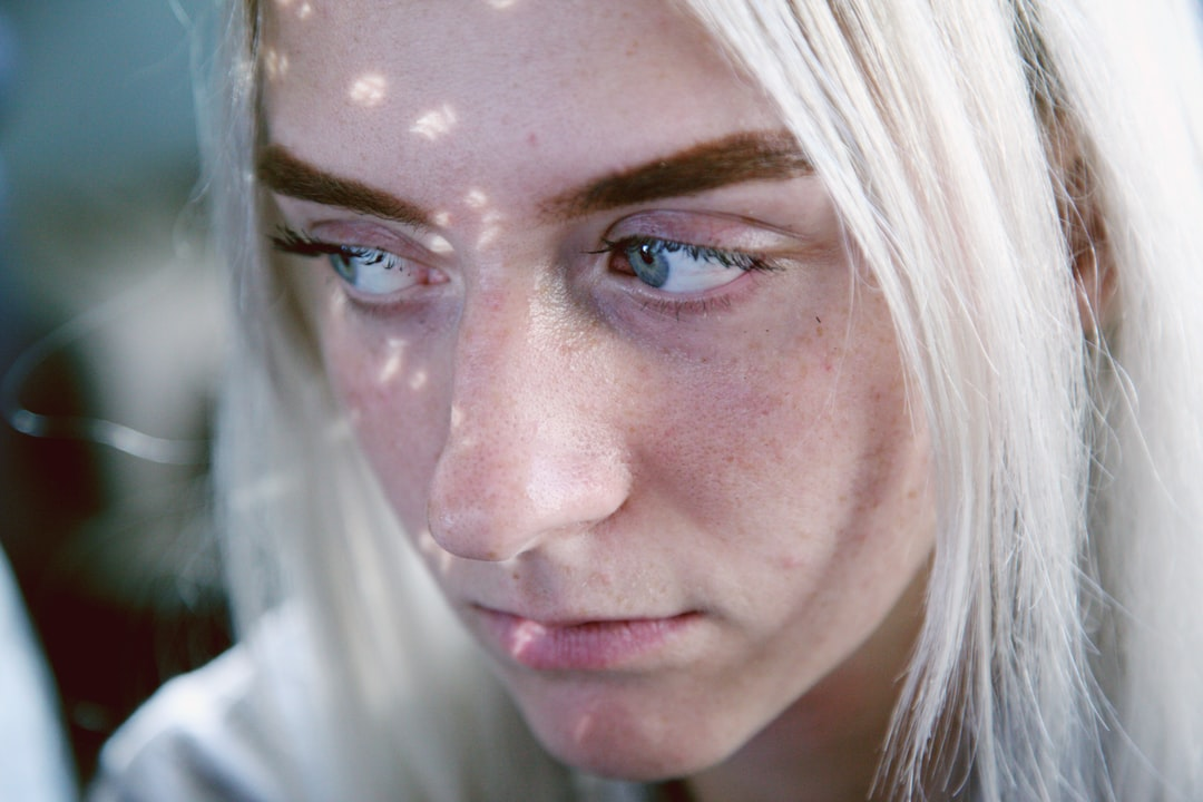 A portrait of an 18 year old young woman in speckled light with a cinematic vibe.