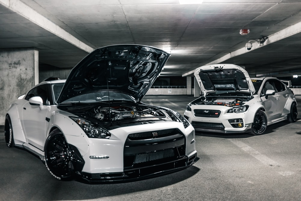two white cars with open hoods