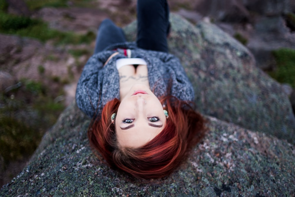 close-up photography of woman lying on rock at daytime