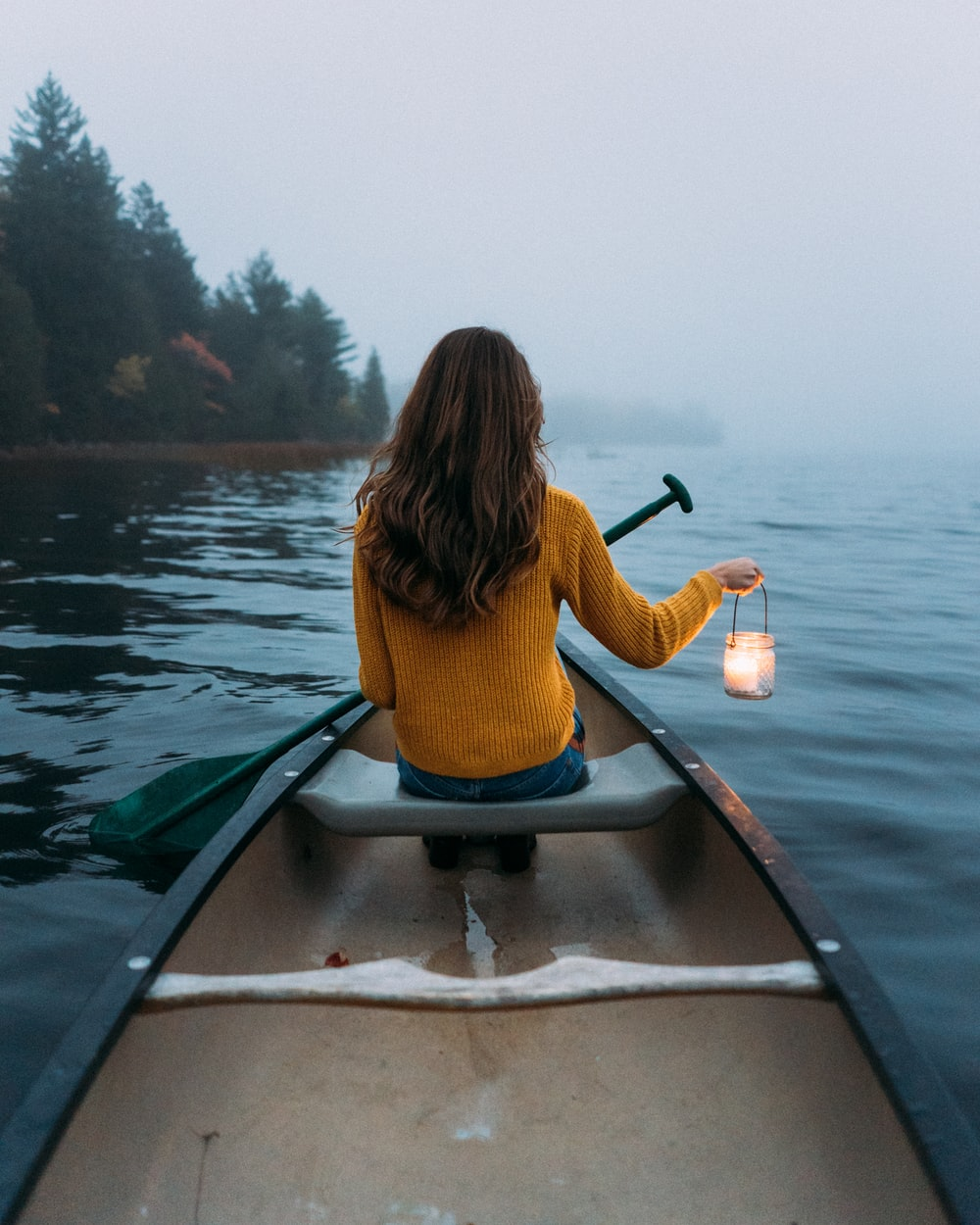 woman sitting and holding lamp on wooden canoe viewing calm body of water