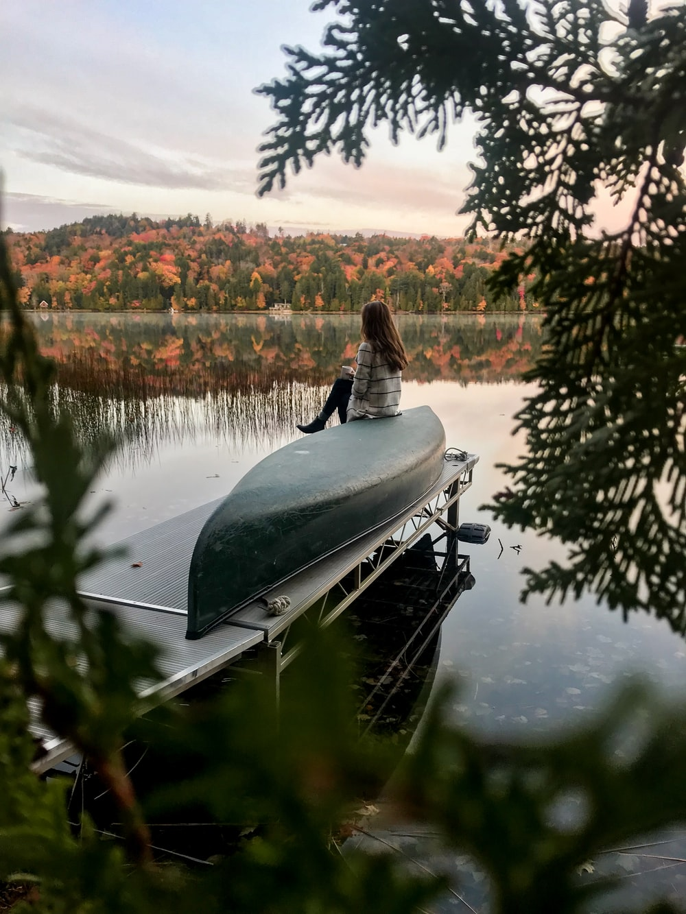 woman in sweater sits on green boat on dock