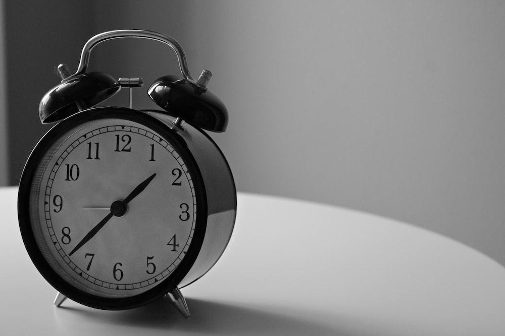 1:37時間を表示する目覚まし時計の白黒写真
