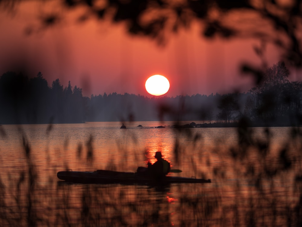 boating man on calm water during golden hour