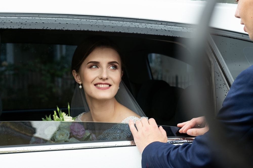 woman wearing wedding dress inside car while smiling