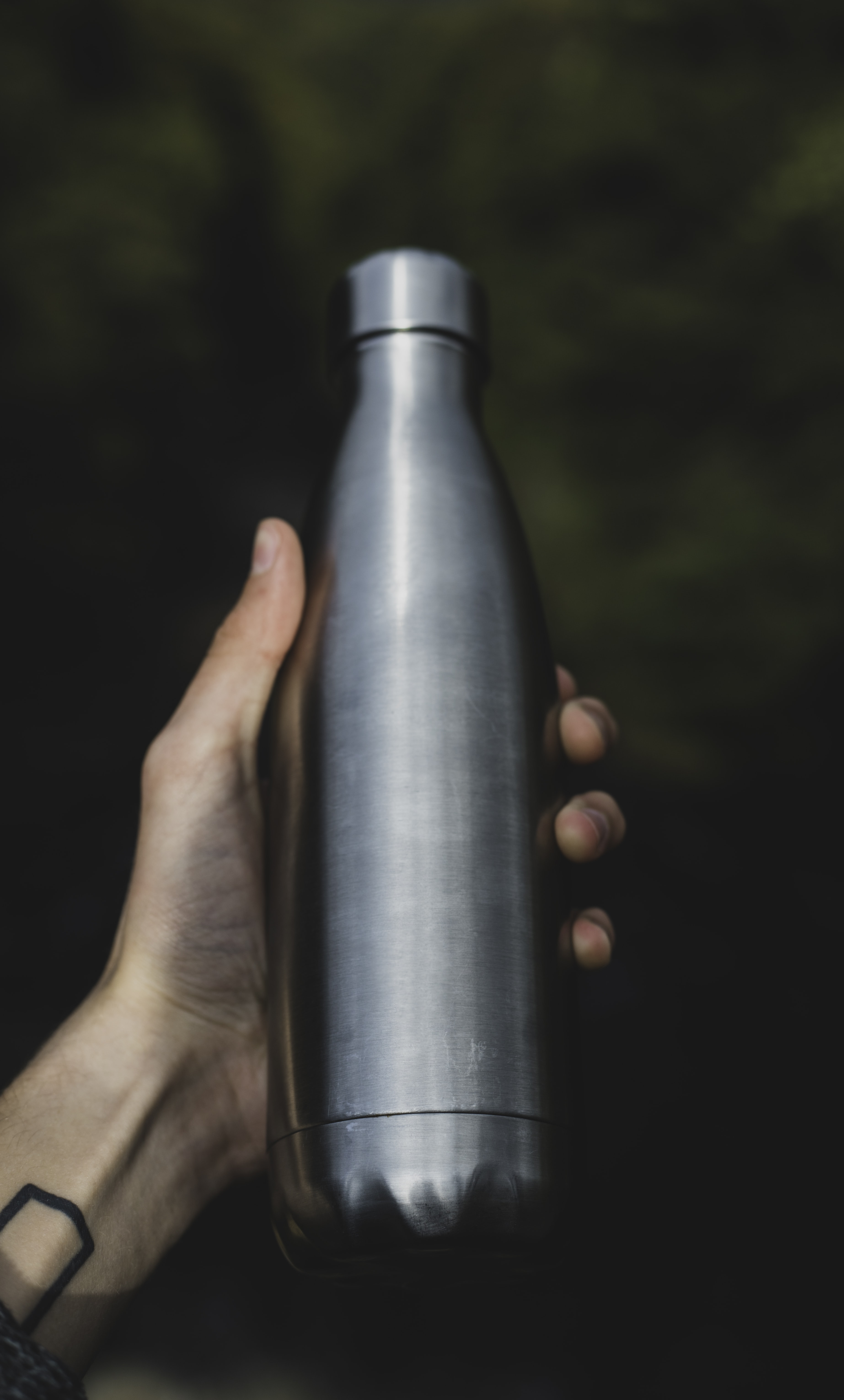 person holding gray bottle