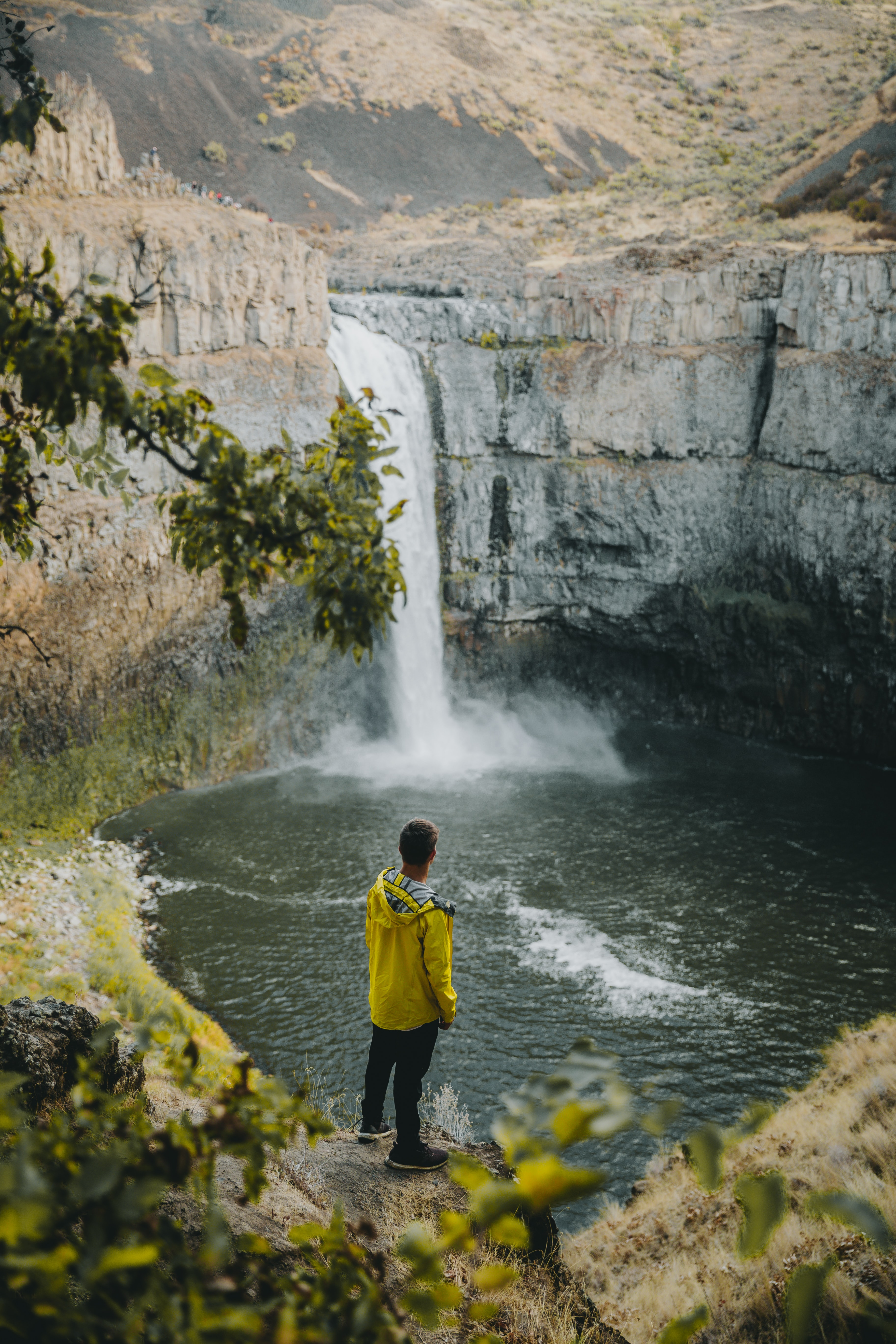 person standing near waterfall during daytime
