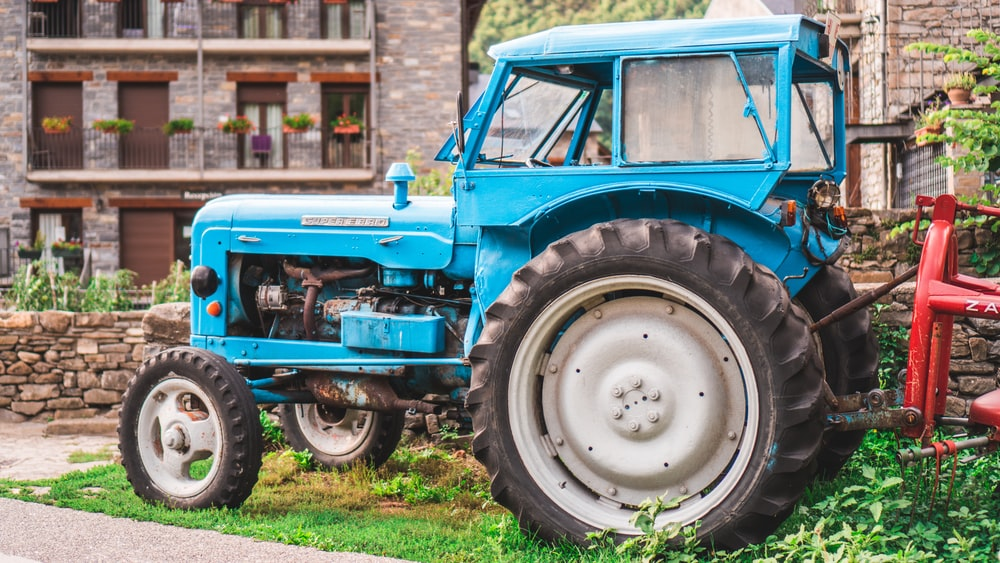 blue tractor parked outside house