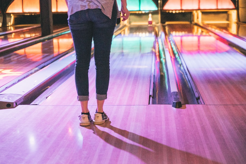 woman in blue jeans standing in front of bowling bay
