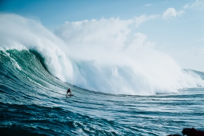 person riding on surfboard with waves behind seascape teams background