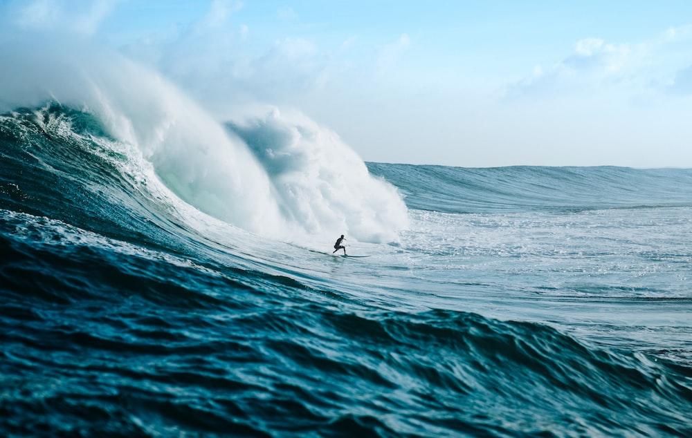 man surfing towards sea waves