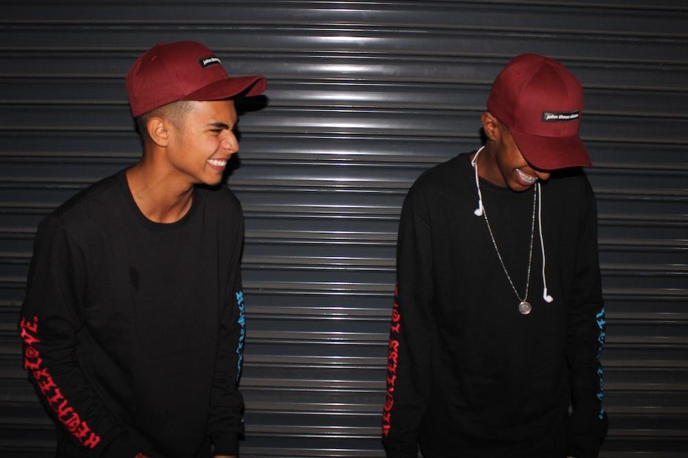 smiling two men standing front of door shutter