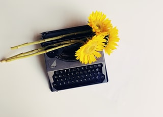 black typewriter with yellow flowers on top