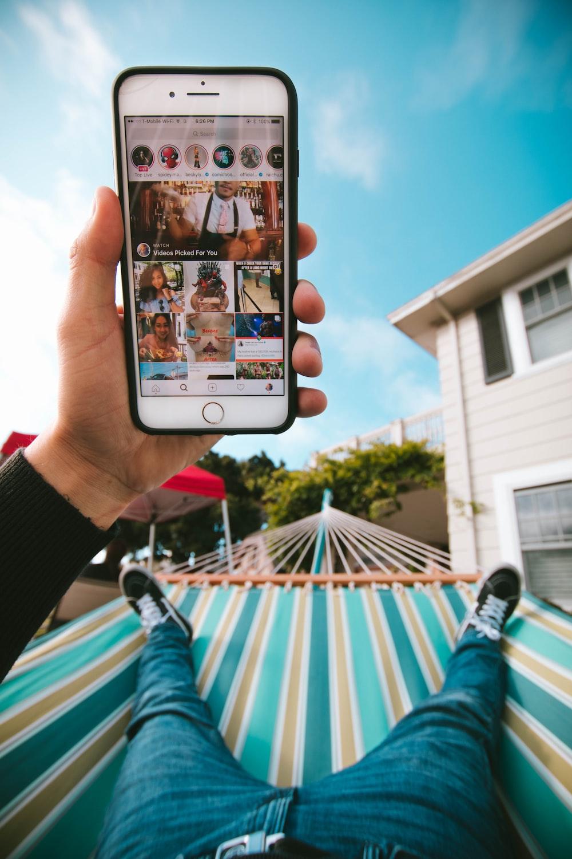person on hammock using iPhone