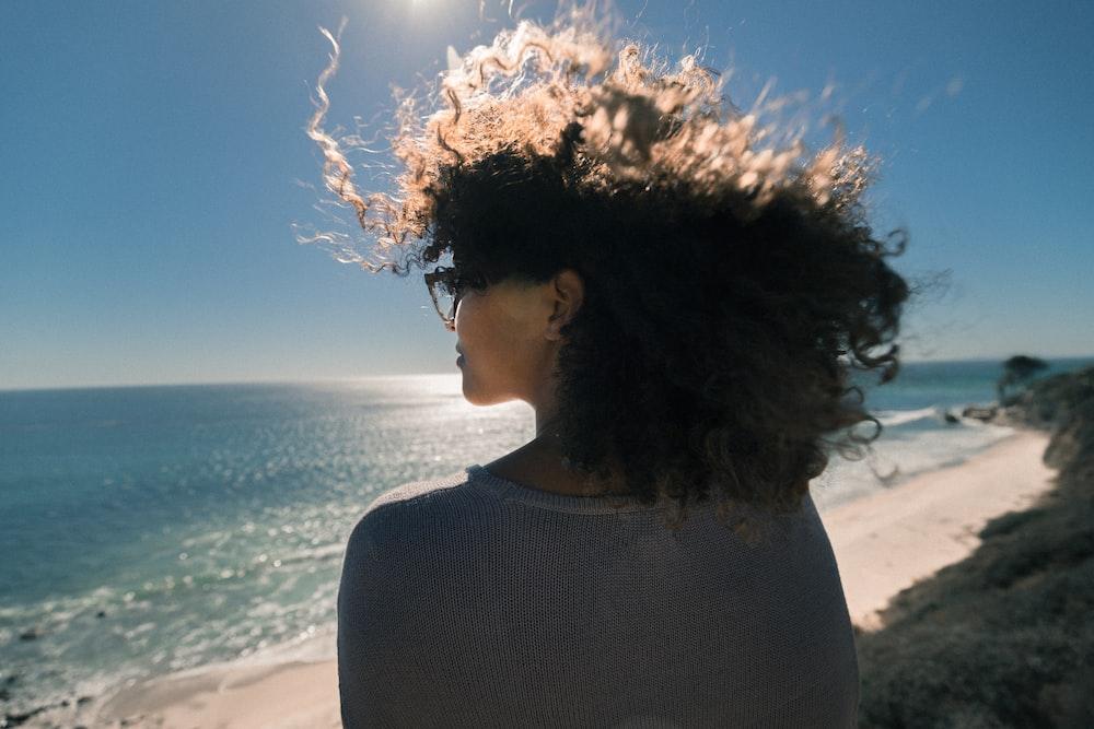 woman wearing gray shirt overlooking at ocean