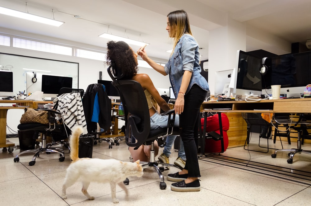 woman wearing denim jacket doing makeup on girl
