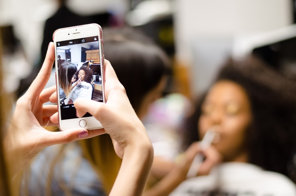 selective focus photography of person taking photo of woman having face make over using phone
