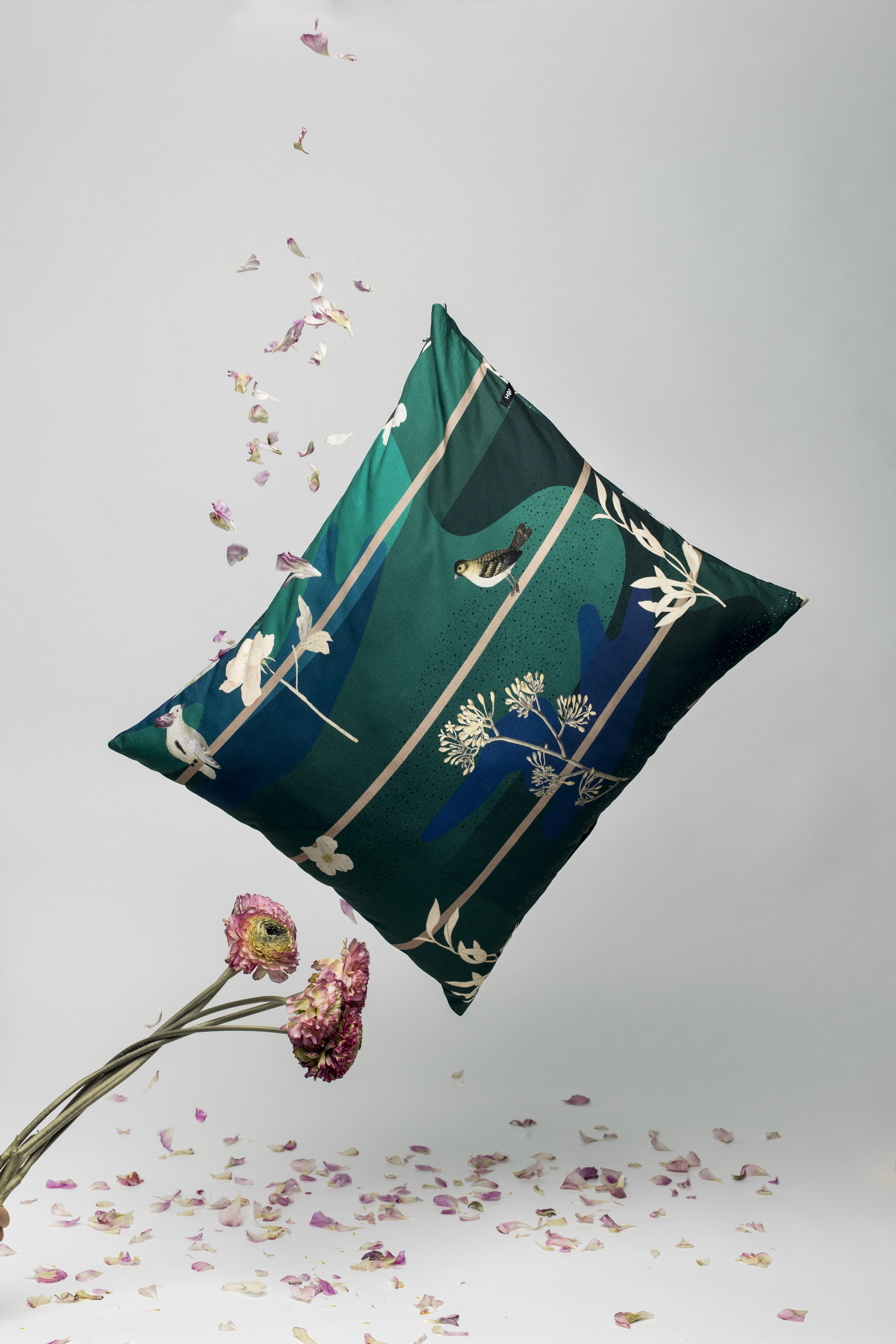 green, beige, and white floral pillow on white surface