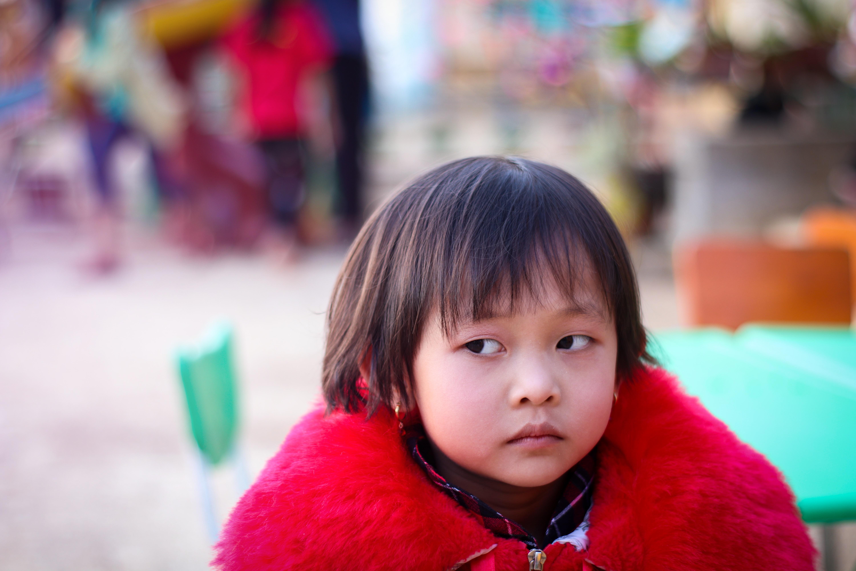 tilt shift focus photography of girl in red fur coat