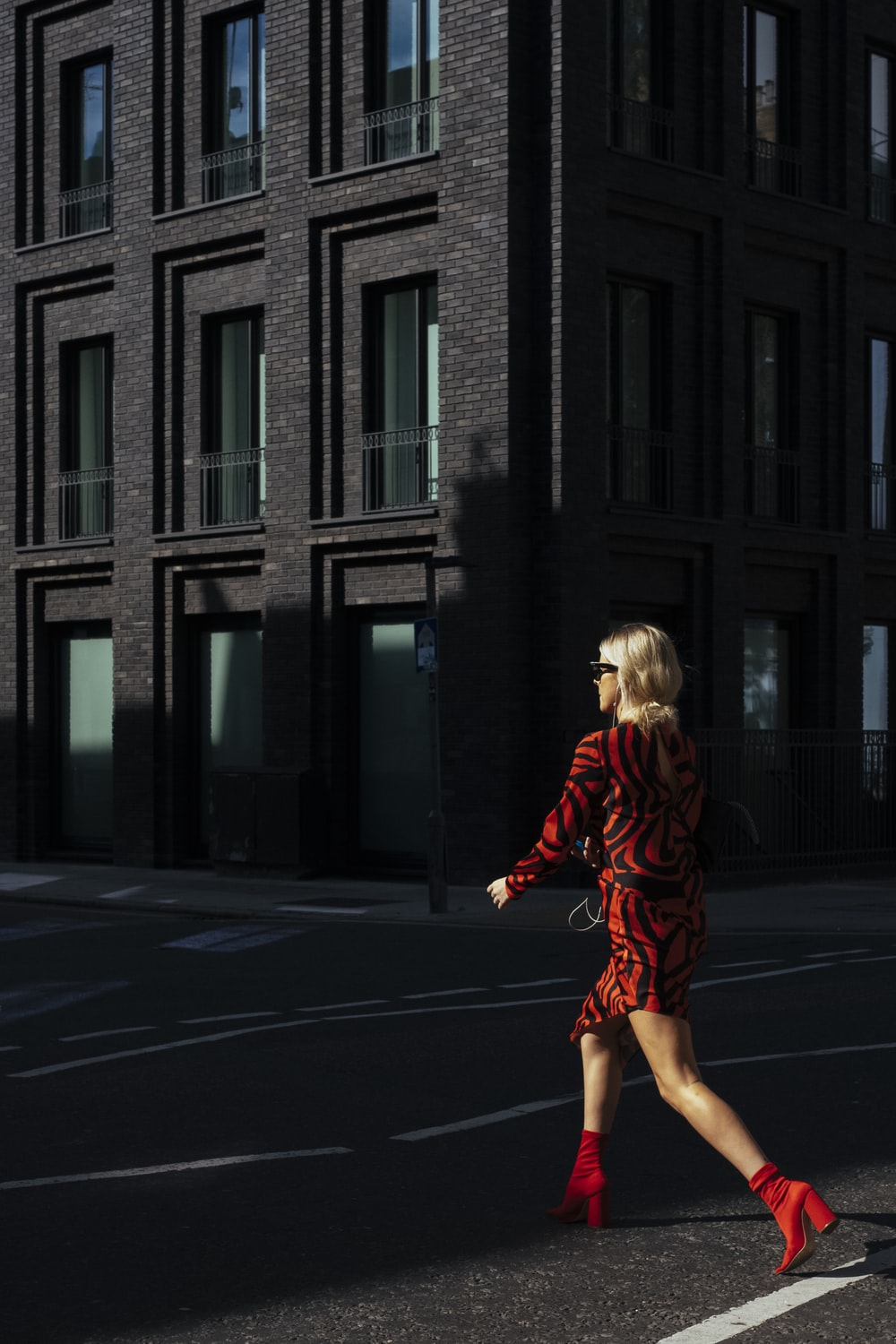 woman crossing the street during daytime
