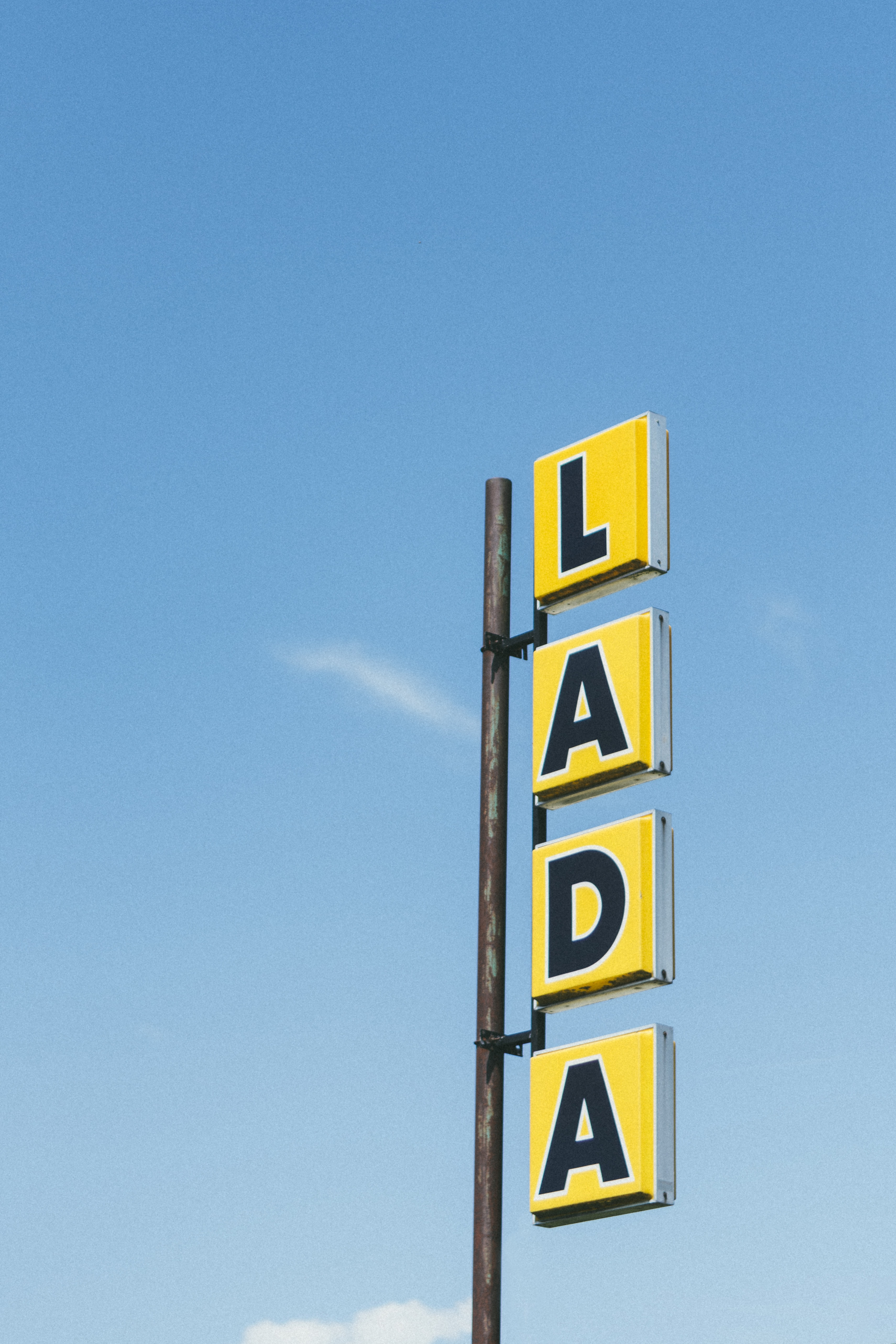 yellow and black lada signage under blue sky