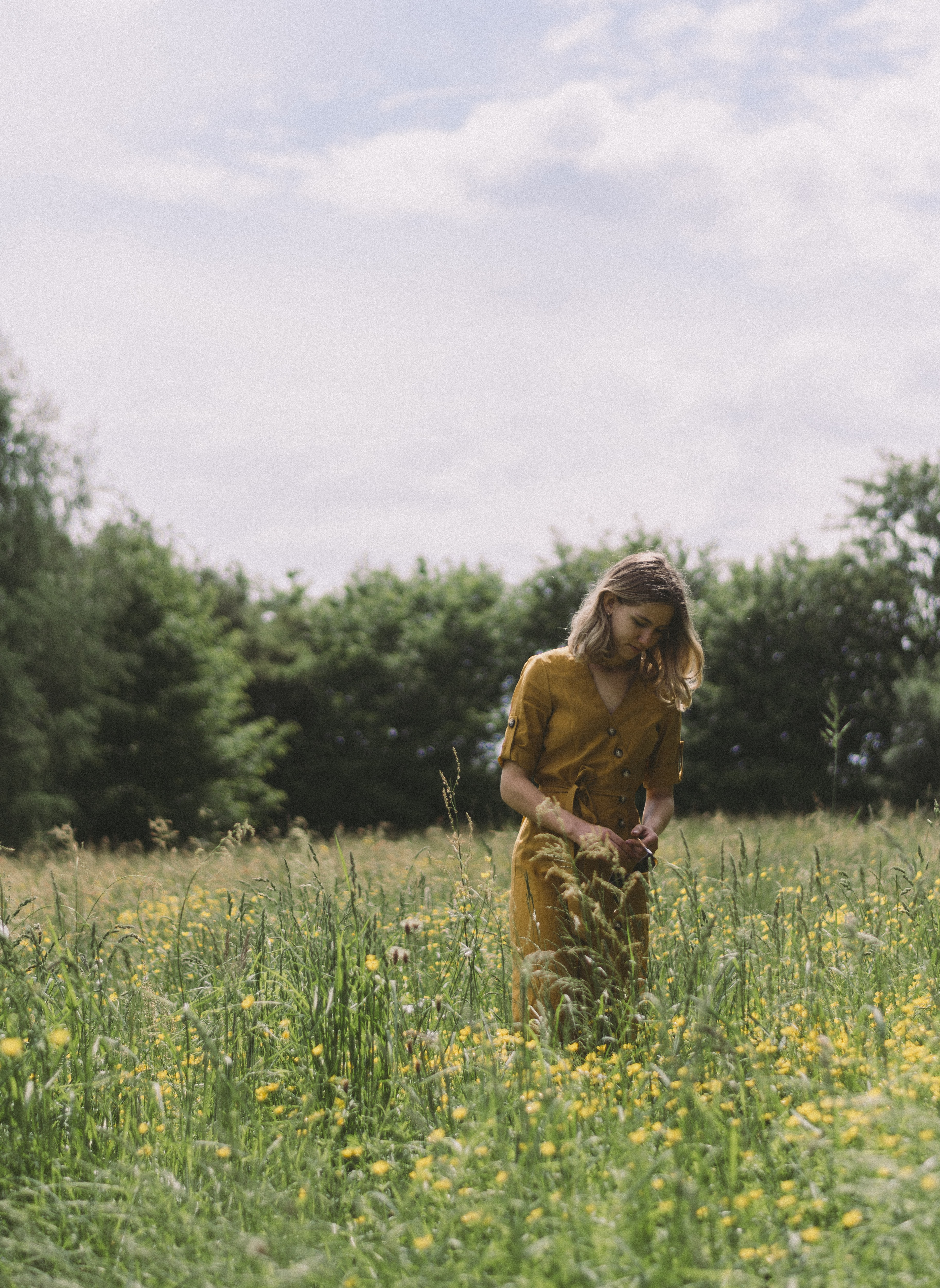 woman wearing brown V-neck dress standing on the flower field