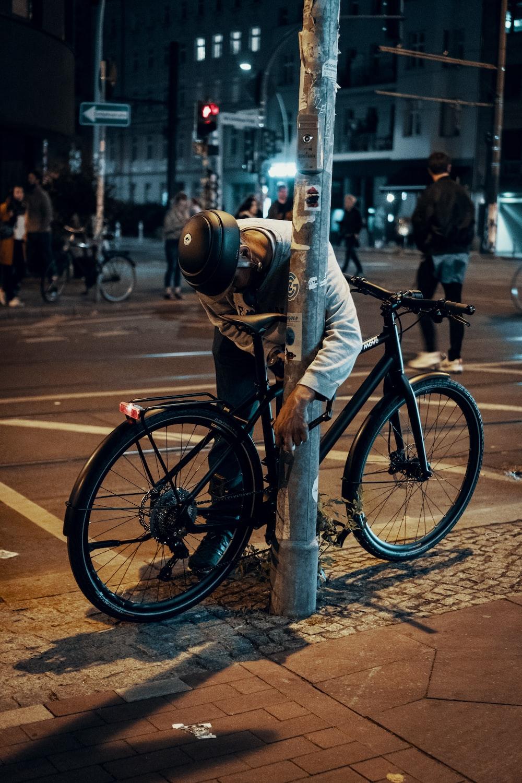 man standing beside bicycle