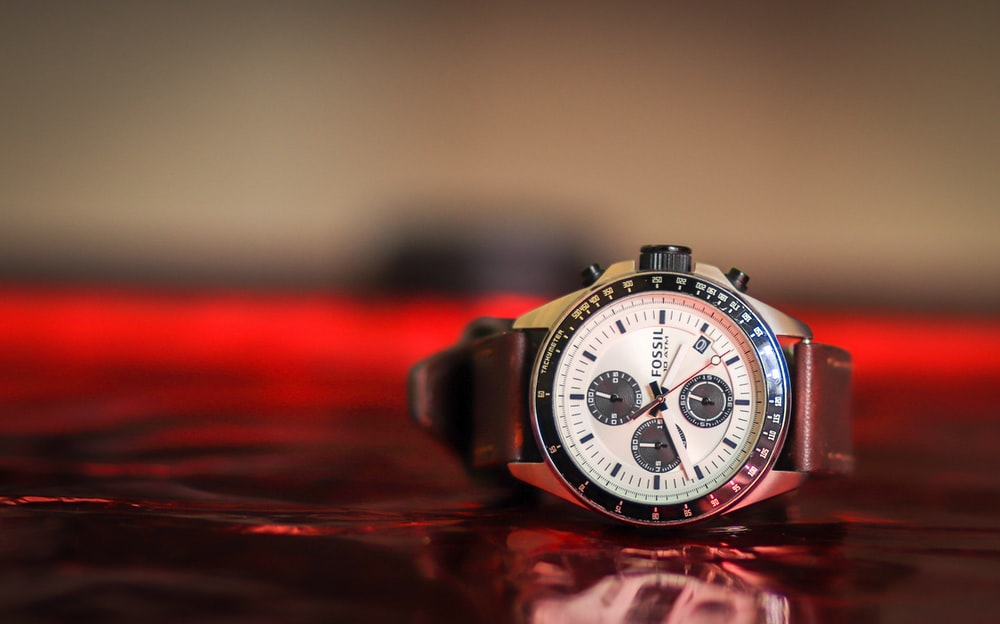 round black and white Fossil chronograph watch with brown leather band displaying at 10:42