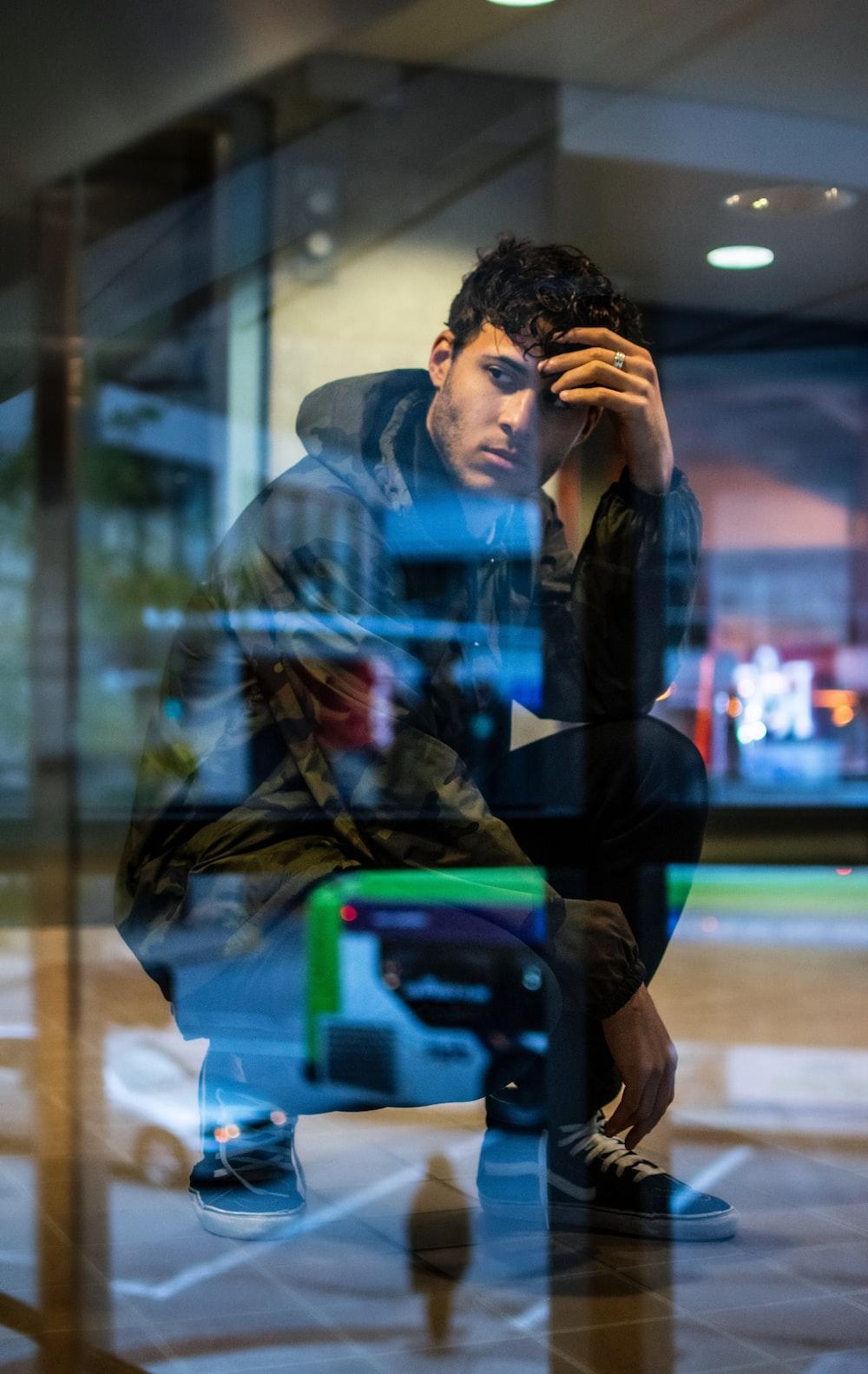 man in black hoodie sitting near window