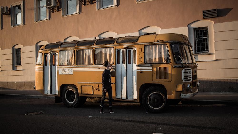 man standing beside yellow bus