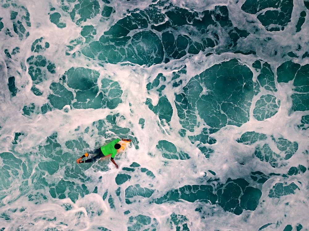 high-angle photography of man riding on surfboard