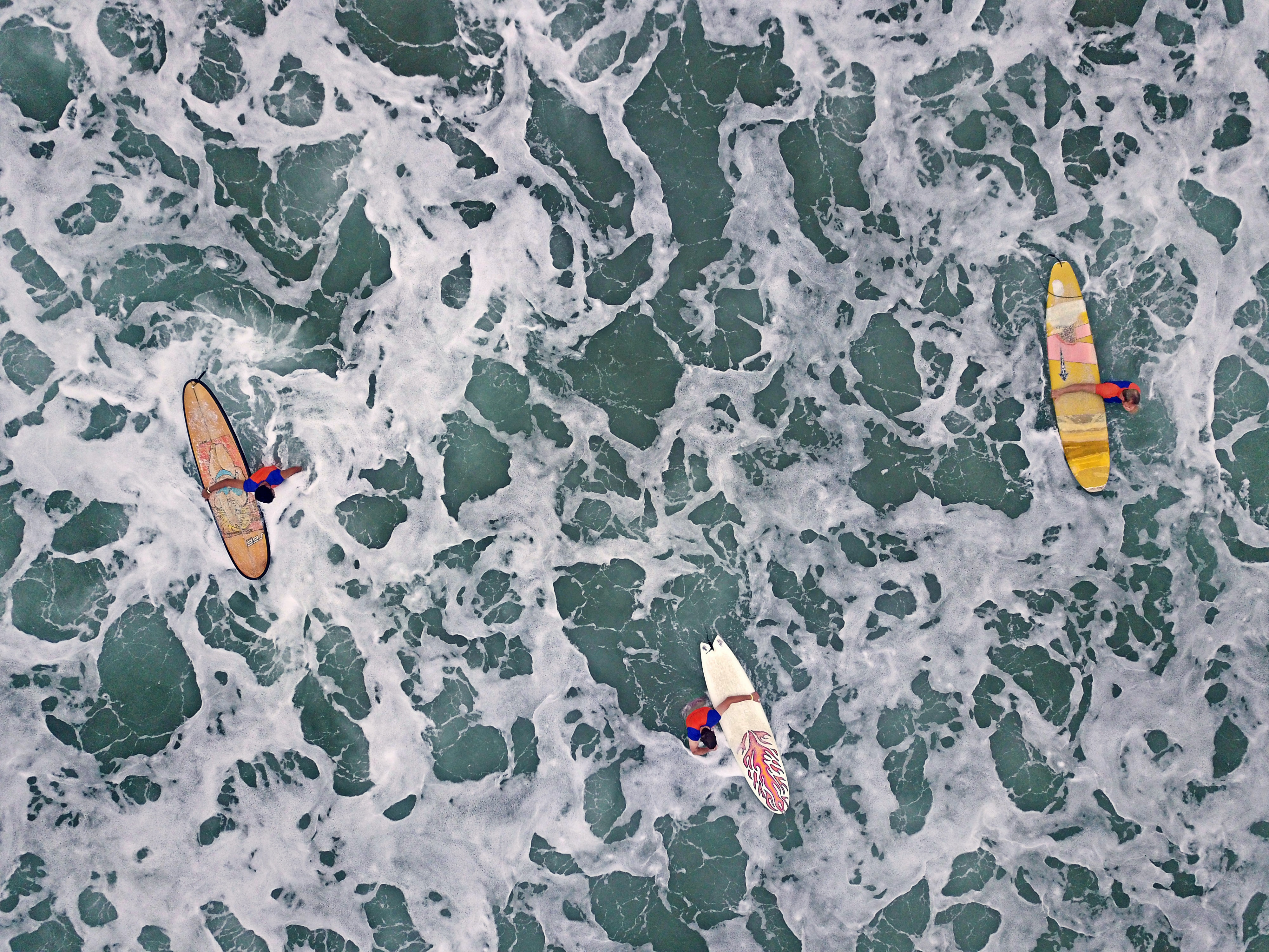 aerial view of people carrying surfboards