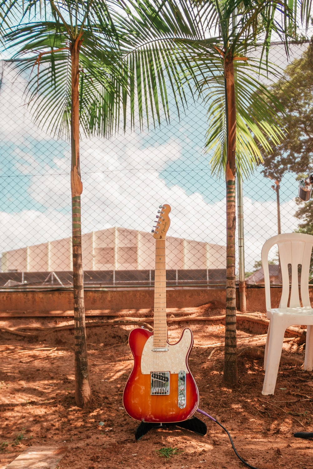 brown and white electric guitar near monobloc chair and trees during daytime