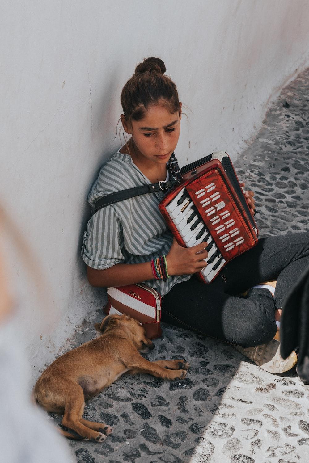 woman playing accordion beside laying dog during daytime