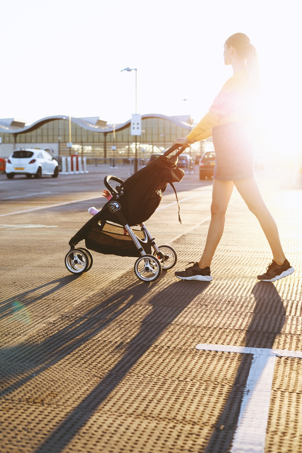 woman pushing baby's stroller on parking area