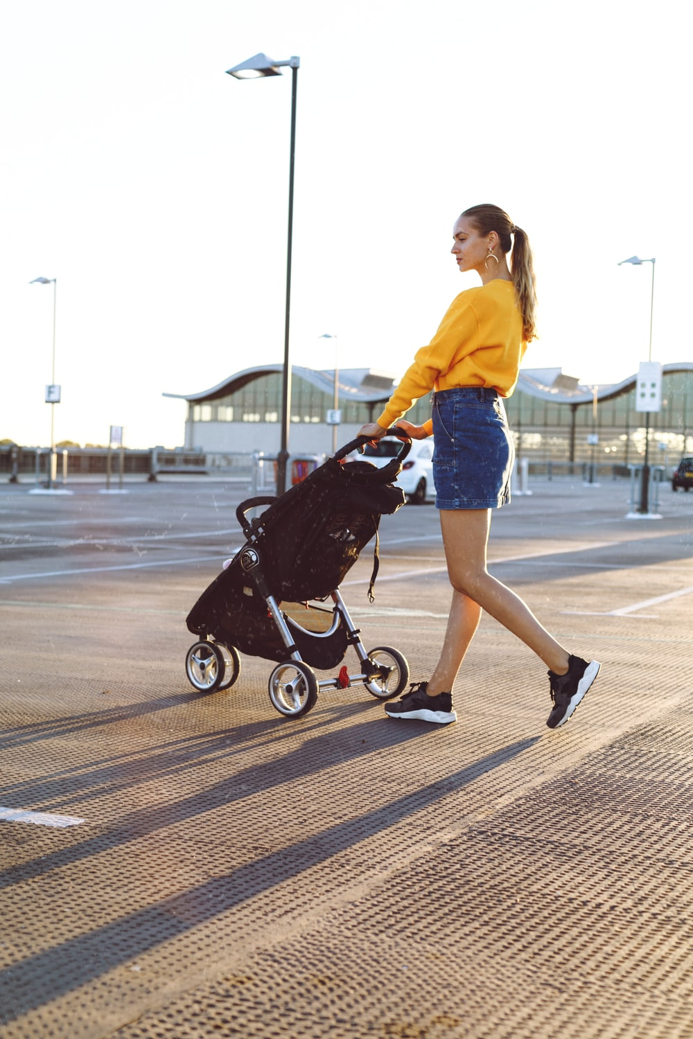 woman holding stroller during daytime