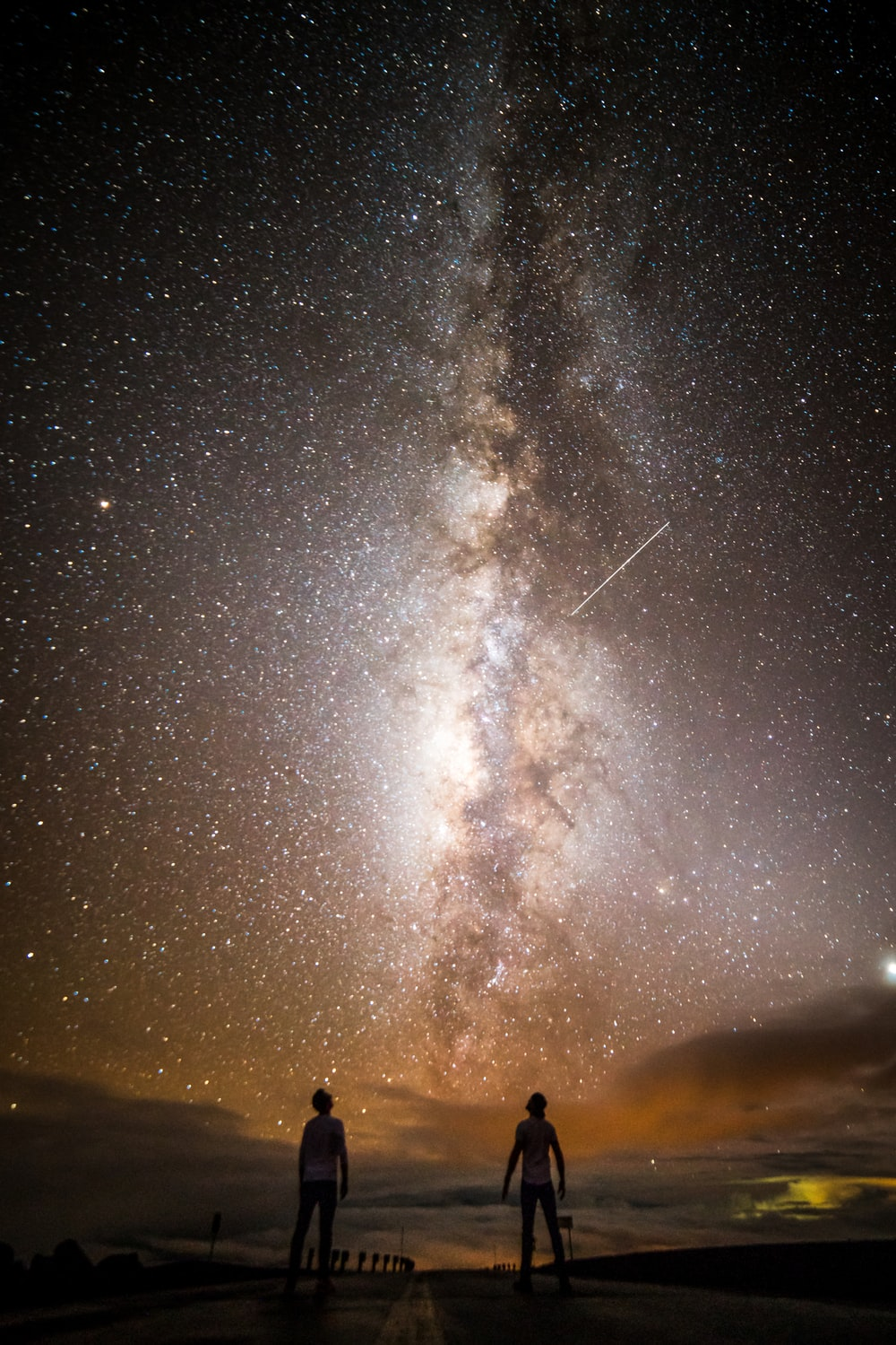 two people standing under milky way at night