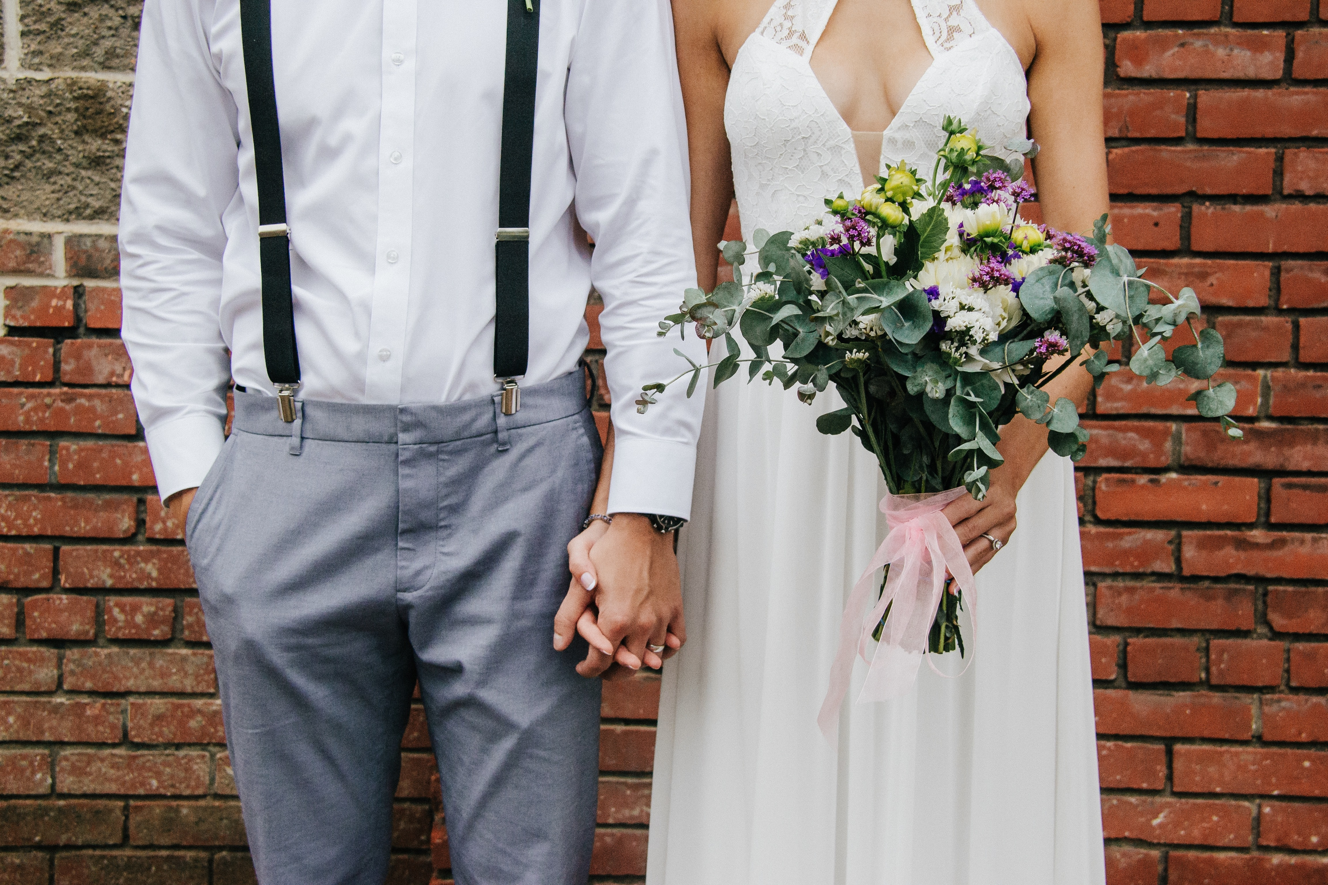bride and groom holding hands and standing beside brown bricked wall during daytime
