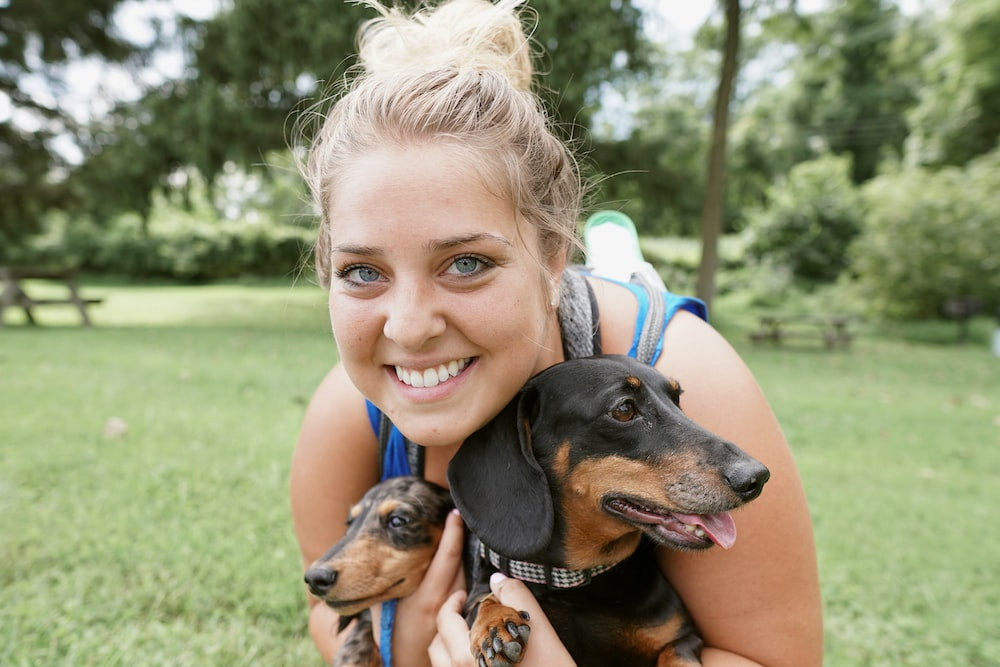 woman carrying two puppies