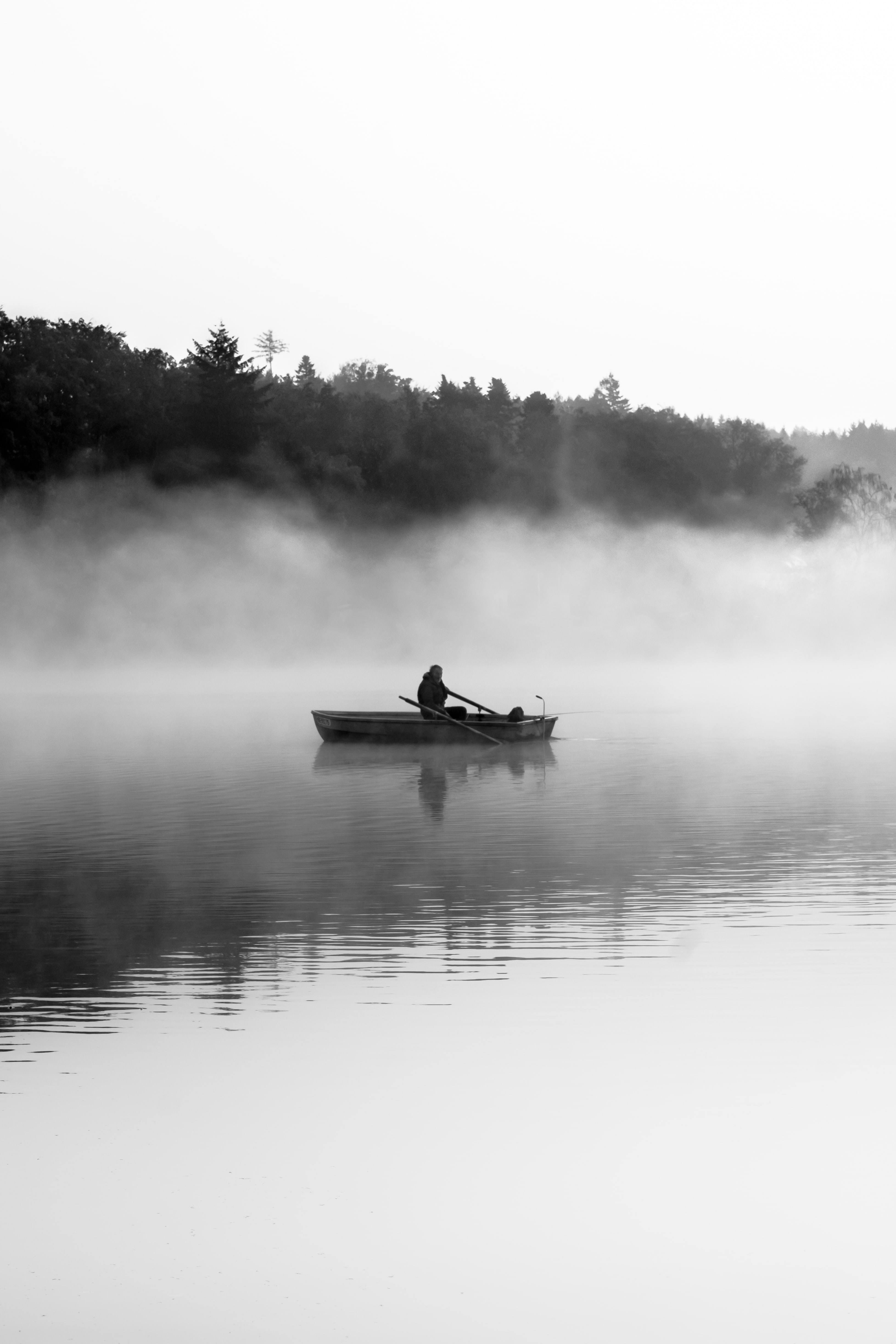 man riding on boat grayscale photo