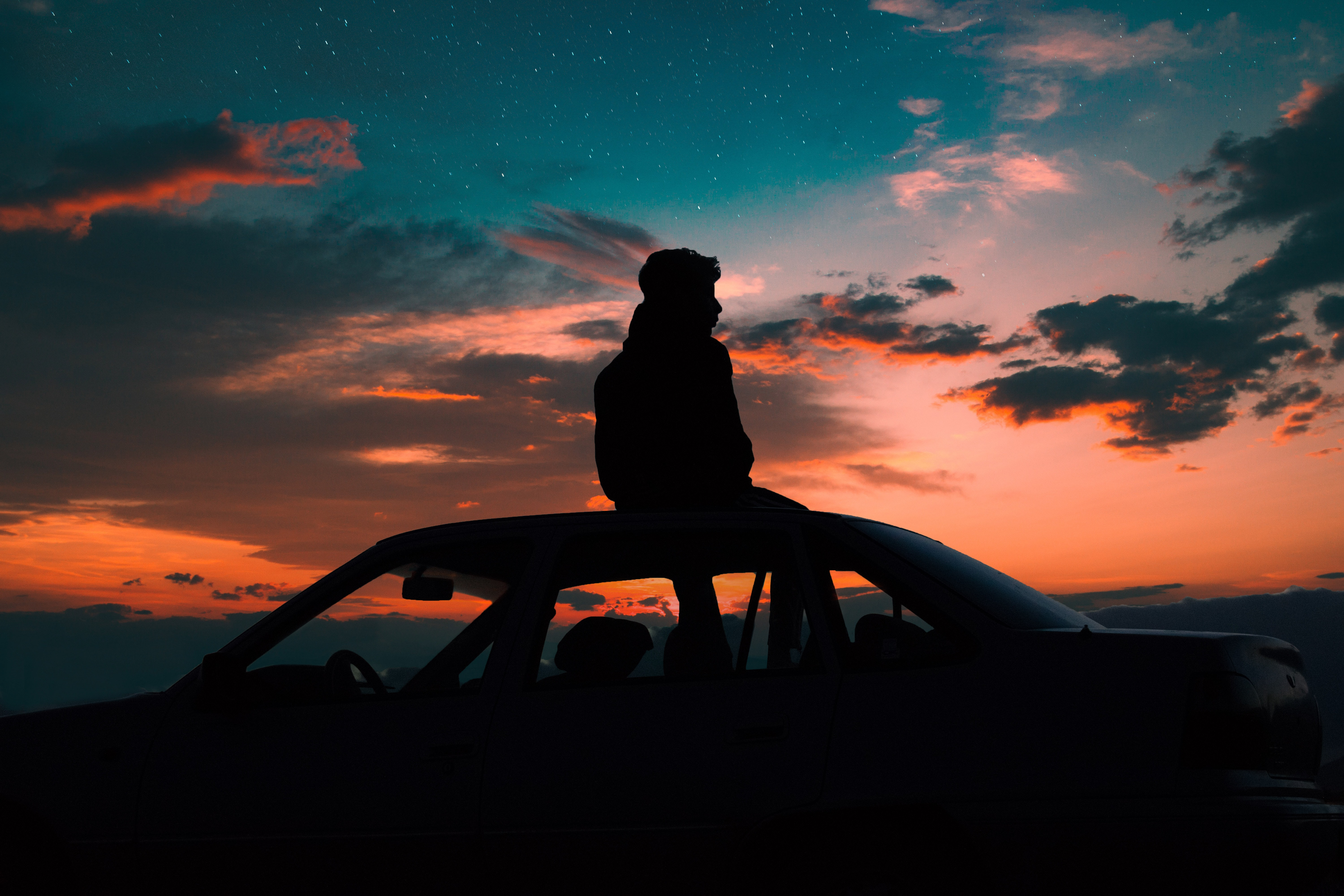 silhouette of man sitting on car roof